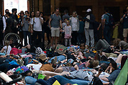 Environmental campaigning group Extinction Rebellion stage a die in at the Natural History Museum on 22nd April 2019 in London, United Kingdom. Hundreds of protesters played dead in the main hall of the world famous museum, to represent a mass extinction of humanity.