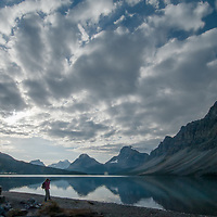 A photographer shoots beside Bow Lake in Banff National Park.  Behind are (L to R)  Mount Andromache, Mount Hector, Bow Peak, Bow Crow Peak and Crowfoot Mountain.