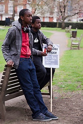 © Licensed to London News Pictures. 31/03/2012. London, England. Londoners led by Lee Jasper and Zita Holbourne of BARAC, today, 31 March, protested outside the U.S. Embassy in Grosvenor Square against the shooting of black hooded youth Trayvon Martin by George Zimmermann in Sanford, Florida. Two black London teenagers watch the protest from Grosvenor Square. Photo credit: Bettina Strenske/LNP