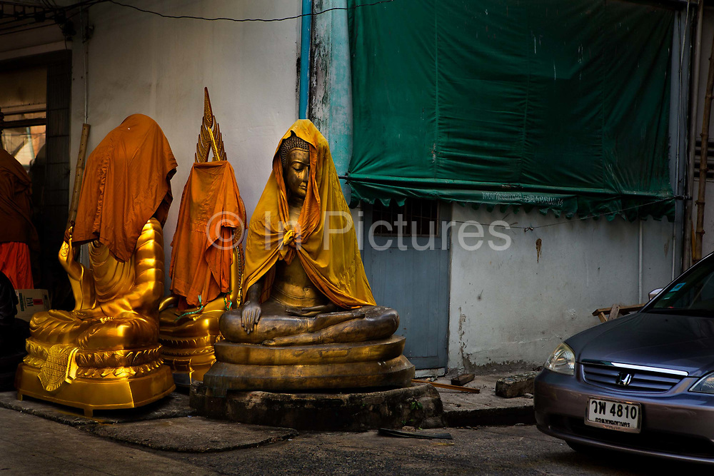Partly covered in traditional orange cloth, religious figures are displayed on the street. Situated in the heart of Bangkok, near the famous swing, is a series of streets and alleyways dedicated to the manufacture of Buddhist and Hindu icons together with other religious paraphernalia.