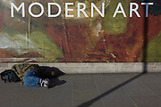 A sleeping man lies in front of the broad message on a hoarding announcing the next major exhibition by Delacroix at the National Gallery in London.