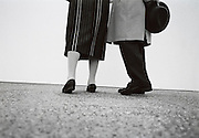 Legs and feet of an elderly couple while they look at a painting