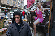 Kem, a Trader at Brick Lane Market with his raunchy poster to his store room, depicting a black woman getting out of a sports car wearing a short pink dress. Kem has been trading here for a very long time.
