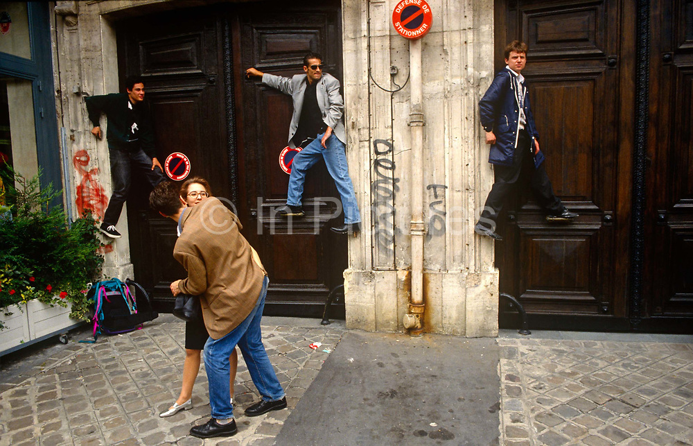 A moment of street theatre is seen as a man seemingly gropes a young woman on the pavement (sidewalk) as three other Parisians gain an advantage by climbing higher than ground level to watch the patriotic Bastille Day Procession from a doorway on the Avenue Champs-Élysées, Paris. The young men have lodged themselves awkwardly a metre above the ground, resting their feet on various door catches and ledges, as if floating in mid-air. On a street traffic sign the French words 'Defense de Stationner' are written which in English translates as 'No Stopping', referring to vehicles not pedestrians. There is graffiti tagging sprayed on the walls and a brown stain at the bottom of a drainpipe.