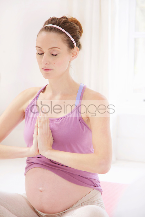 Pregnant Woman Meditating with Hands Together