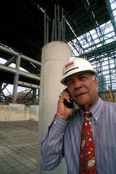Construction Manager Talks on Cell Phone at Construction Site