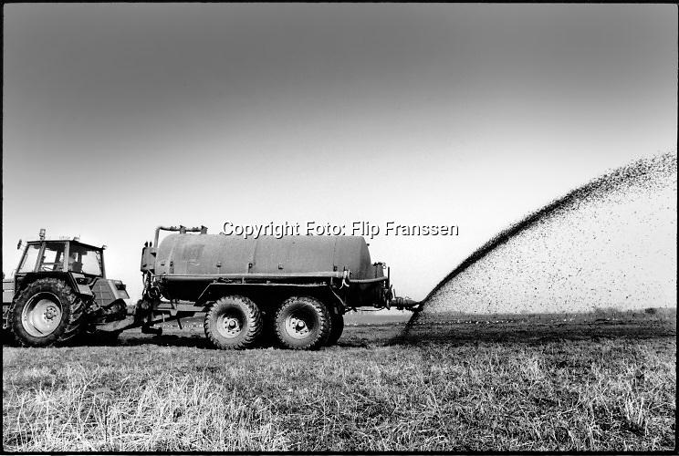 Nederland, Persingen, 15-3-1992Een boer rijdt vloeibare mest uit over het land . Vanuit de tank wordt de mest op het land gespoten met een grote waaier.Foto: Flip Franssen