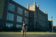 """BIRMINGHAM, AL – SEPTEMBER 10, 2015: Quintarius Monroe stands in front of Woodlawn High School following football practice. A type 1 diabetic, Monroe requires frequent blood sugar testing and supervision when self-administering insulin. When care from qualified personnel at his school in Center Point became unavailable, Monroe was forced to transfer several miles away from his locally zoned school to attend Woodlawn High School. The Americans with Disabilities Act requires schools to provide """"reasonable accommodation"""" for students with medical conditions, but given that most schools no longer retain school nurses, many schools are failing to provide adequate care for their students.<br /> CREDIT: Bob Miller for The New York Times"""