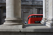 Commuter and Red London Routemaster bus beneath Cornhill pillar and the wall of the Bank of England.