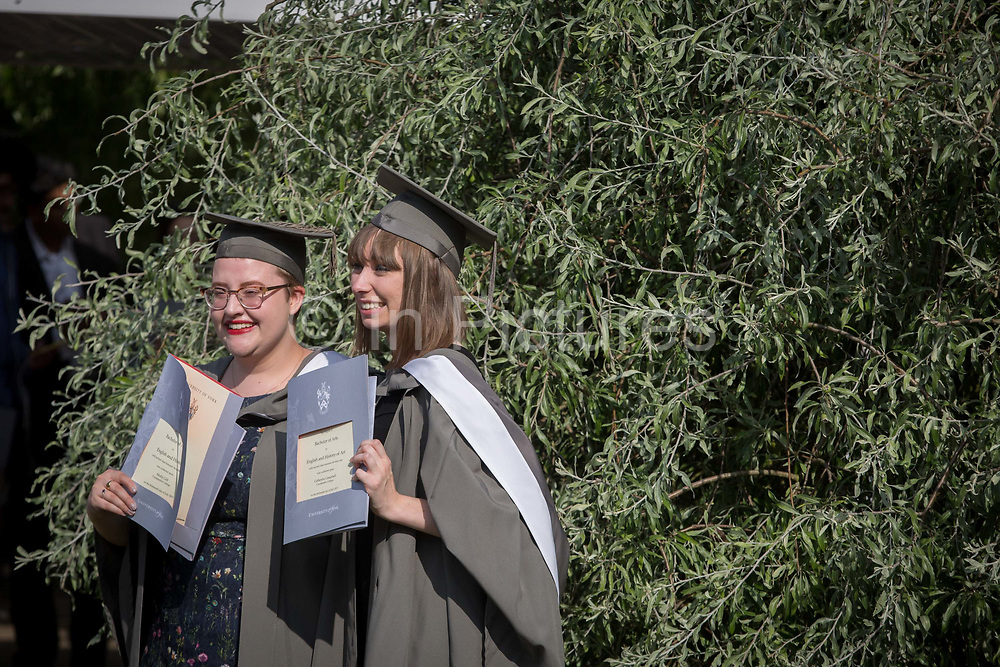Young women graduates wearing rented gowns and mortarboards have photos taken by family members after their university graduation ceremony, on 13th July 2017, at the University of York, England.