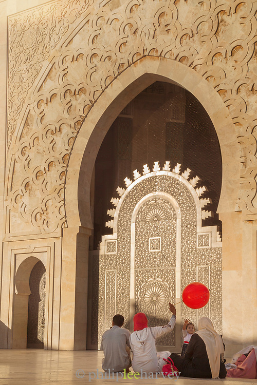 Rear view of candid family moment in front of Hassan II Mosque in Casablanca, Morocco