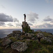 Rob, one of the researchers on Round Island, stands atop a rock on the Summit of the island at sunset.