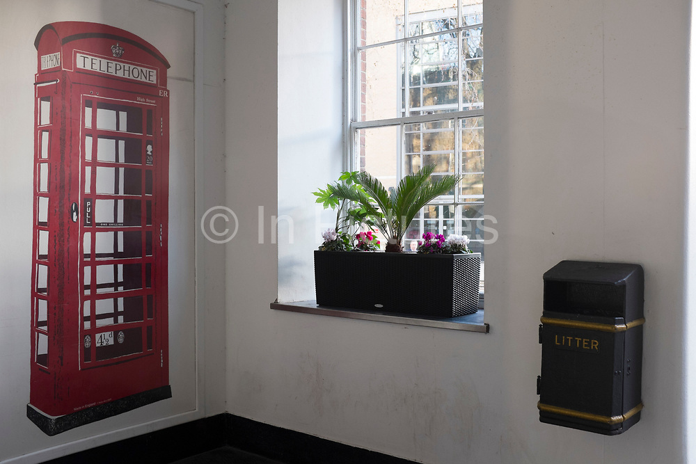 Mural of a red telephone box inside a building at King's College London, UK.