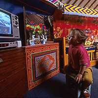 MONGOLIA,Wealthy nomadic family members watch Russian programming on  solar-powered satellite television.