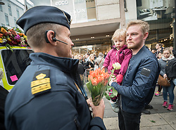 10 April 2017, Stockholm, Sweden: Commemoration of the victims of terror, on Drottninggatan (Queen Street) in central Stockholm, three days after a lorry was driven into a store in central Stockholm, killing at least four people and injuring many more. Here, Police officer Tomas Koppelman-Hellgren receiving flowers as a token of gratitude for the Police's efforts during the attack of the preceding Friday. Parental consent obtained. Oral consent obtained from Police officer and parent, confirming that Church of Sweden and the World Council of Churches may use this photo.