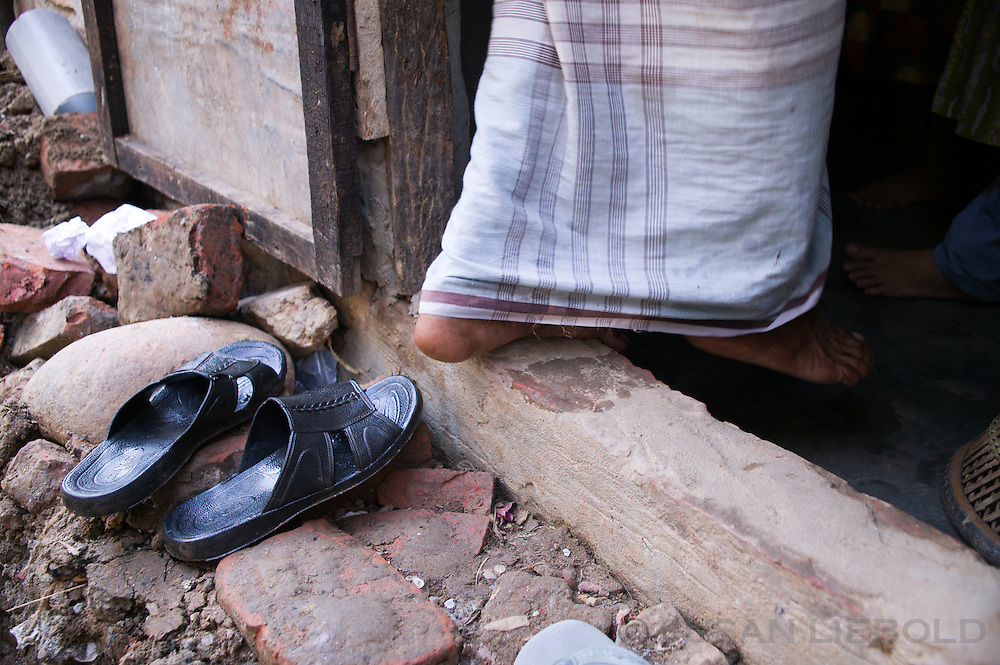 Jalal takes off his shoes before entering his one room home.