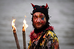 © Licensed to London News Pictures. 06/01/2013. London, UK. A member of the 'Bankside Mummers' dressed as 'Beelzebub' poses for cameras next to the Thames during the annual 'Twelfth Night' Celebration in London today (06/01/13). The tradition, a pagan celebration of the new year and the end if Christmas, takes place every year at Bankside outside the Globe Theatre and sees the actors of the Bankside Mummers perform for the public. Photo credit: Matt Cetti-Roberts/LNP