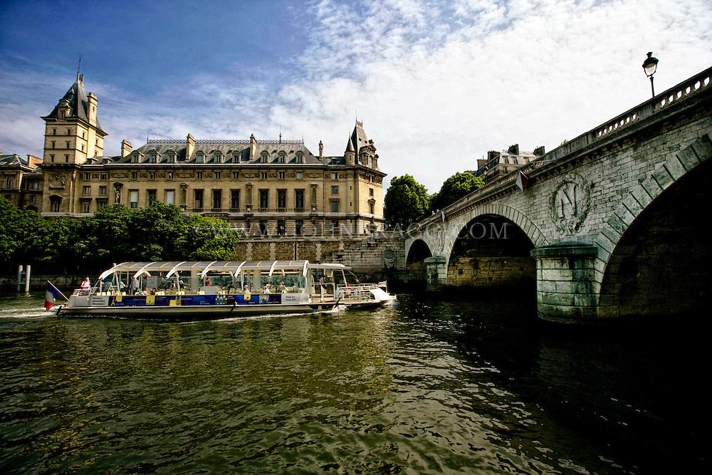 River Boat heading under the Pont Saint Michel Bridge, Paris France.