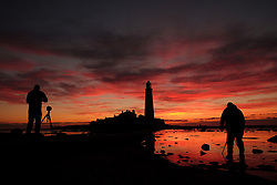 Photographers line up their shot as the sun rises at St. Mary's Lighthouse, Whitley Bay.