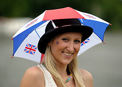 © Licensed to London News Pictures. 27/06/2012. Henley-on-Thames, UK A woman wears a hat to protect her from the rain. Spectators watch rowing crews compete at the Henley Royal Regatta on June 26, 2012 in Henley-on-Thames, England. The 172-year-old rowing regatta is held 27th June- 1st July 2012. Photo credit : Stephen Simpson/LNP