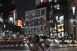 "September 28, 2016 - Tokyo, Tokyo, Japan - Protestor has a sign reads Ã'Review the agreement between America and JapanÃ"" during the demonstration against the construction of a new U.S. military base in Okinawa. The Executive Committee Stop Henoko organized the demonstration as the Abe government continues to put pressure on Okinawa to allow the project to proceed. (Credit Image: © Alessandro Di Ciommo via ZUMA Wire)"