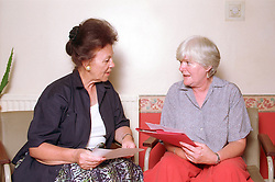 Two female counsellors discussing and comparing case notes,