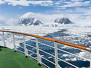 Sea ice floats in the Southern Ocean offshore from tidewater glaciers on Graham Land, the north part of the Antarctic Peninsula, in Antarctica. See a vast frozen wilderness from the railing of an Antarctic cruise ship.