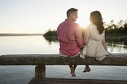 Mature couple looking at each other on pier at sunset, Bavaria, Germany