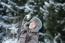 Young man throwing snowball in winter, Bavaria, Germany