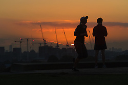 Primrose Hill, London, October 4th 2016. The sun rises above the distant clouds as dawn breaks across London, throwing the figures of joggers into silhouette.