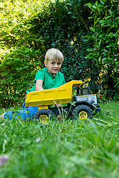 Young boy playing with toy car in the garden