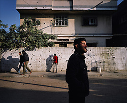 People are seen outside a home marked with shrapnel from Israeli artillery fire, Beit Hanoun, Gaza Strip, Palestinian Territories, Nov. 23, 2006. According to Human Rights Watch, since September 2005, Israel has fired about 15,000 rounds at Gaza while Palestinian militants have fired around 1,700 back.