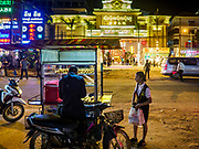 """13 FEBRUARY 2019 - SIHANOUKVILLE, CAMBODIA:  A Cambodian worker at the MGM Casino buys food from a street vendor after her shift. The MGM is a Chinese owned casino. There are about 80 Chinese casinos and resort hotels open in Sihanoukville and dozens more under construction. The casinos are changing the city, once a sleepy port on Southeast Asia's """"backpacker trail"""" into a booming city. The change is coming with a cost though. Many Cambodian residents of Sihanoukville  have lost their homes to make way for the casinos and the jobs are going to Chinese workers, brought in to build casinos and work in the casinos.      PHOTO BY JACK KURTZ"""