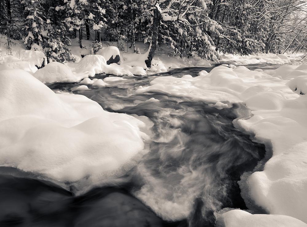 Stream flowing through freshly fallen snow, northern Vermont