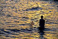 Boy with toy sailboat at sunset, Candi Dasa Beach, Bali, Indonesia
