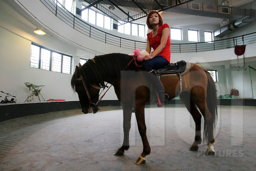 A circus performer sits on horseback to train for her next act, Vietnam, Southeast Asia