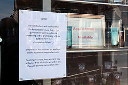 Covid 19 - Sign in a closed hairdressers  window in a market Town in Dorset during lock down, UK March 2020