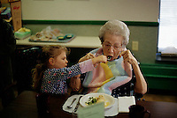 2002, Minneapolis, Minnesota, USA --- Four-year-old Manui Franken feeds her grandmother Phoebe Franken at a nursing home. --- Image by © Owen Franken/CORBIS