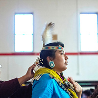 Clara Nakai, left, affixes the collar of Ashley Nakai before the traditional talent category during the 2018 Saint Michael Indian School Princess Pageant in St. Michael Thursday.