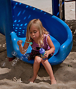 Young Blonde Girl Blowing Bubbles At The Park
