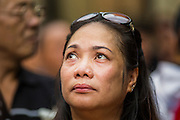 28 APRIL 2014 - BANGKOK, THAILAND:  A woman weeps during the funeral for Kamol Duangphasuk, 45, in Bangkok. Kamol was a popular poet who wrote under the pen name Mai Nueng Kor Kunthee. Kamol had been writing since the 1980s and was an outspoken critic of the 2006 coup that deposed Thaksin Shinawatra. After the 2010 military crackdown against the Red Shirts he went into temporary self imposed exile fearing for his safety. After he returned to Thailand he organized weekly protests against Thailand's Lese Majeste laws, which he said were being used to stifle dissent. Kamol was shot and murdered on April 23. The assailants are still at large but the murder is thought to be political.    PHOTO BY JACK KURTZ