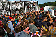 New York Brass Band playing in front of Shepard Fairey Obey posters in the Hell arena, Shangri La field, Glastonbury Festival 2016. The Glastonbury Festival is the largest greenfield festival in the world, and is now attended by around 175,000 people. Its a five-day music festival that takes place near Pilton, Somerset, United Kingdom. In addition to contemporary music, the festival hosts dance, comedy, theatre, circus, cabaret, and other arts. Held at Worthy Farm in Pilton, leading pop and rock artists have headlined, alongside thousands of others appearing on smaller stages and performance areas.
