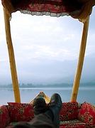 Man relaxing on a shikara, a local wooden boat, on Lake Dal, Kashmir, India