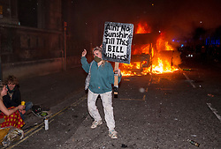 """© Licensed to London News Pictures;21/03/2021; Bristol, UK. Protestors watch and pose with a sign which is a pun on both the  Police, Crime, Sentencing and Courts Bill and a song by Bill Withers, in front of a police van which has been set on fire as police clash with protesters outside New Bridewell Police Station on Sunday evening during a """"Kill the Bill"""" protest against Police, Crime, Sentencing and Courts Bill takes place through the centre of Bristol during the Covid-19 coronavirus pandemic in England. The Bill proposes new restrictions on protests. Lockdown restrictions have been partly lifted to allow people to gather outdoors socially in households, bubbles, or to meet one person from another household, but the police say protests are not allowed under the current Covid regulations. Photo credit: Simon Chapman/LNP."""
