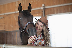 Portrait of a young woman stroking her brown horse in barn and smiling, Bavaria, Germany