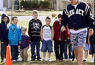 First grader Adam Kotzian (3rd L) watches instructions from physical education teacher Mark Glen with his classmates at Eagleview Elementary school in Thornton, Colorado March 31, 2010.  Adam and his parents are achondroplasia dwarfs but his sister Avery is not.   REUTERS/Rick Wilking (UNITED STATES)