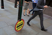 City workers walk past an upside down building site Banksman's lollipop sign that usually tells road-users to allow for turning construction traffic, on Sun Street near Liverpool Street Station in the City of London, the capital's financial district - aka the Square Mile, on 8th August, in London, England.
