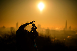 © Licensed to London News Pictures. 29/12/2016. London, UK. A couple take a selfie at unrise over the city of London as seen from Parliament Hill on Hampstead Heath, Hampstead, North London on another cold winter morning. Most of the UK has woken to freezing temperatures. Photo credit: Ben Cawthra/LNP