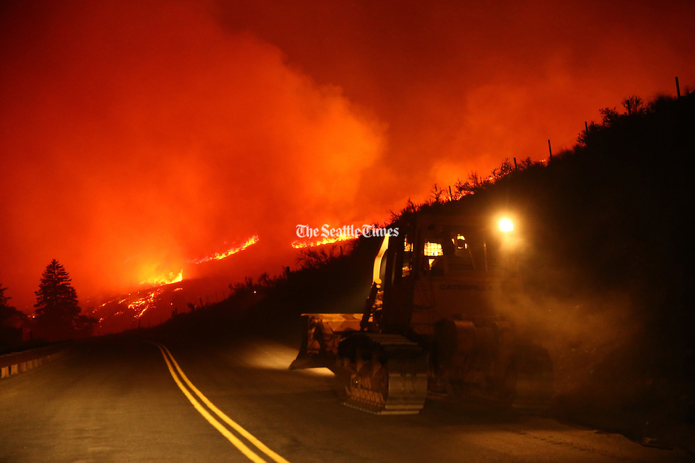 A tractor travels down Twisp River Road just outside of the town of Twisp early in the morning Thursday, Aug. 20, 2015. <br /> <br /> Erika Schultz / The Seattle Times
