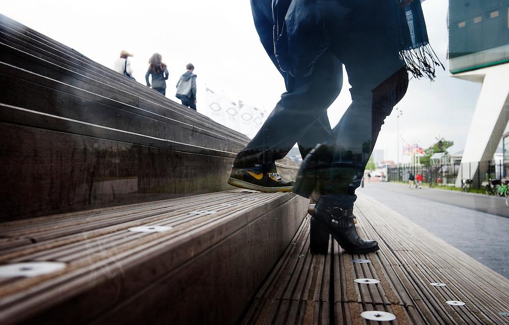 Nederland, Amsterdam, 10 juli 2012.Mensen lopen van de trap van het filmmuseum Eye aan het IJ..Gefotografeerd door reflecterend raam...Foto (c): Michiel Wijnbergh